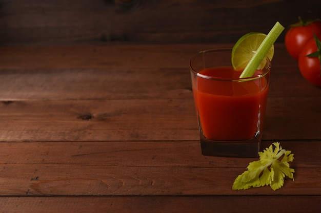 Bloody mary cocktail in glass on wooden background with tomatoes, celery and lime.
