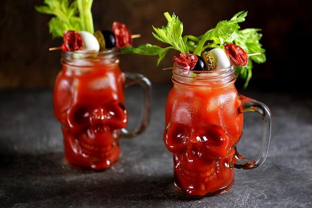 Коктейль кровавая мэри в стеклянном черепе с палочками сельдерея, лаймом и консервированными овощами