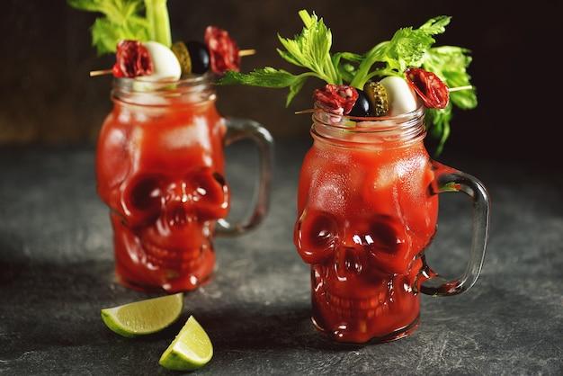 セロリスティック、ライム、缶詰野菜とガラスの頭蓋骨のブラッディマリーカクテル