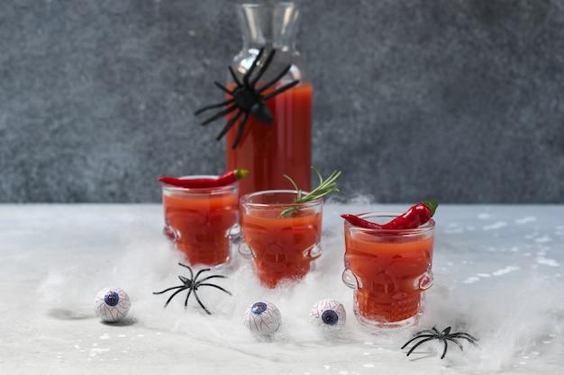 Коктейль кровавая мэри или томатный сок в стаканах в форме черепа