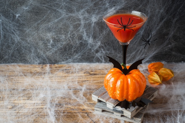 Bloody mary cocktail, pumpkin with bats and spiders for halloween, copyspace