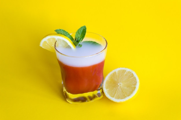 Bloody mary, tomato cocktail with lemon on a yellow