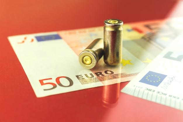 Кровавые деньги на фоне концепции европы, патроны 9-мм пистолета на банкнотах евро