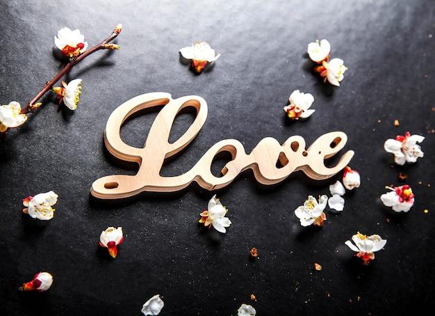 검은 표면에 꽃과 사랑이라는 단어가있는 나무 간판