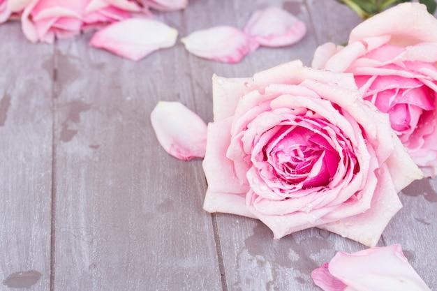Bloomin 핑크 장미 나무 테이블에 누워