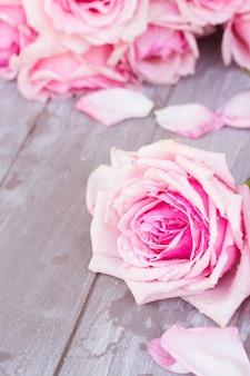 나무 테이블에 누워 꽃잎과 블루 민 핑크 장미