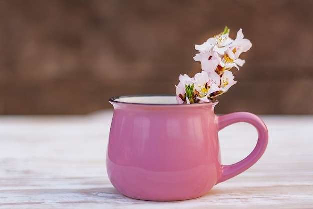 Blooming almond tree twig in a pink cup on a wooden table