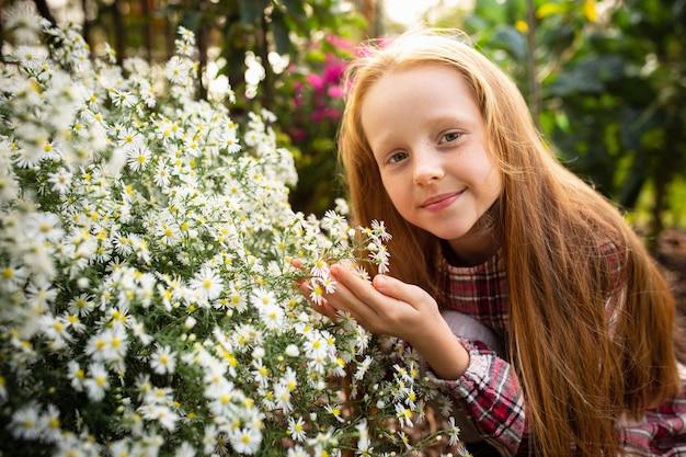 개화하고 빛납니다. 야외 정원에서 꽃과 함께 행복 한 작은 백인 소녀. 사랑, 가족, 생활 방식, 수확, 가을 개념. 쾌활하고 건강하고 사랑스럽습니다. 유기농 식품, 농업, 원예.