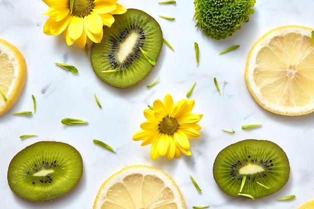自然な黄色の花と新鮮な柑橘系の果物と咲く背景。白地に緑の花びらが付いたフラットレイフラワーパターン。