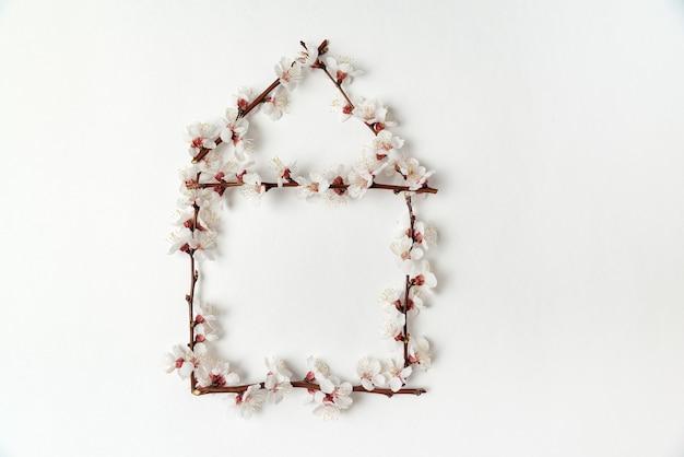 咲く花は白い背景の上の家の形で枝分かれします。テンプレート。背景。モックアップ。