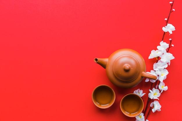 Цветущая ветка рядом с чайным сервизом