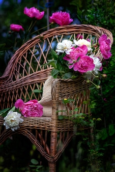 Blooming branches with flowers and peony buds with water drops in a wet garden after the rain