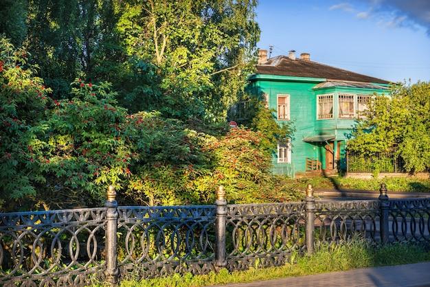 이른 여름 아침에 볼로그다에 있는 정원의 꽃이 만발한 덤불과 녹색 목조 주택의 현관