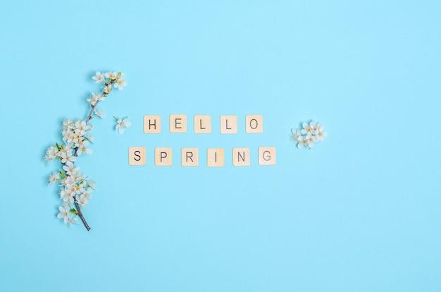 白い花と咲く桜の枝、青い背景にこんにちは春のテキスト。季節性のコンセプト、春。フラットレイ、コピースペース。上からの眺め。 Premium写真