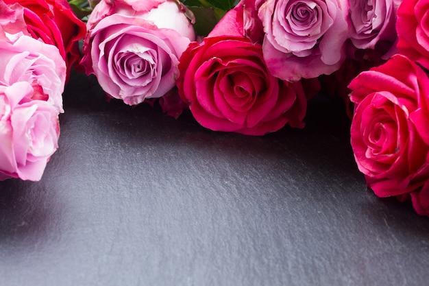 Рамка из цветущих темных и светло-розовых роз на черном столе