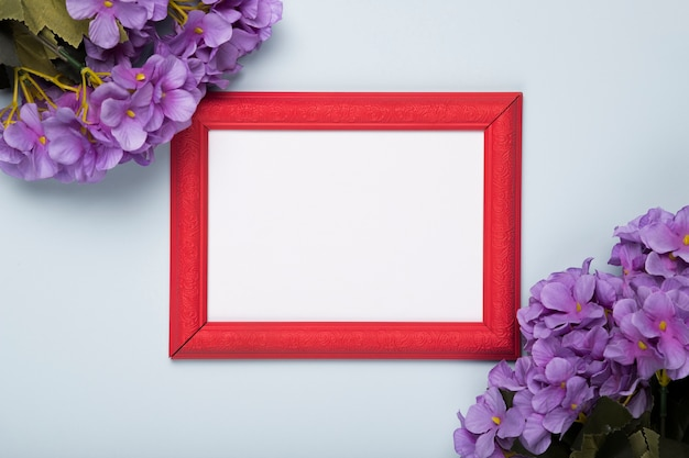 Blooming flowers with frame on table