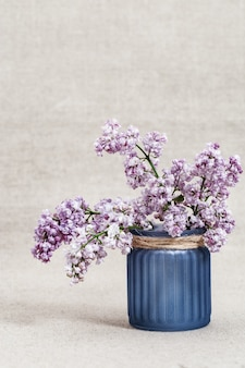 Blooming lilac flowers in glass vase on rustic background with copy. selective focus. vertical format.