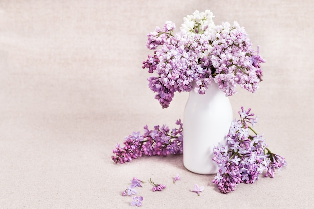 Blooming lilac flowers in white vase on rustic