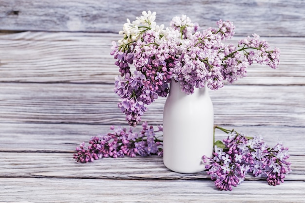 Blooming lilac flowers in white vase on wood