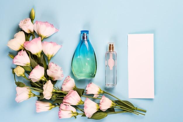咲くピンクトルコギキョウパルファムボトルと一枚の紙、フラットレイアウト。