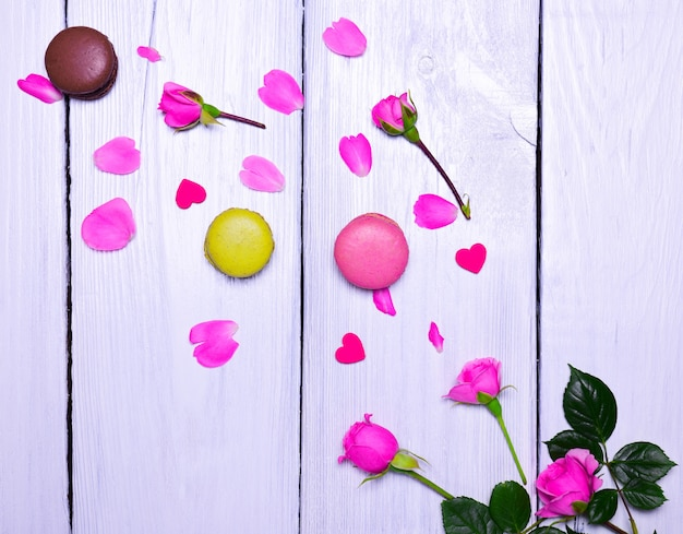 Blooming pink roses and three macaroons
