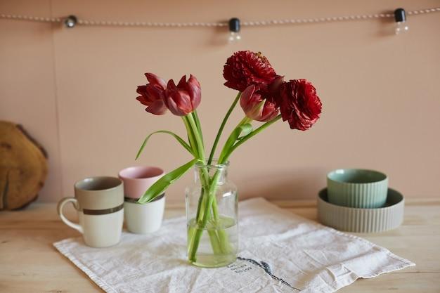 居心地の良いキッチンの木製テーブルにあるガラスの花瓶に咲く赤いチューリップ。花で飾られたキッチンのインテリア。