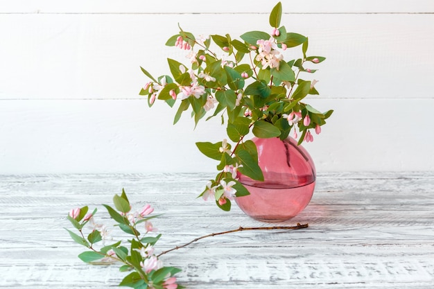 Blooming spring branches of flowers in glass pink vase on wooden vintage white background copy space