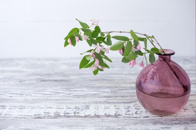 Blooming spring branches of flowers in glass pink vase on wooden white background with copy space