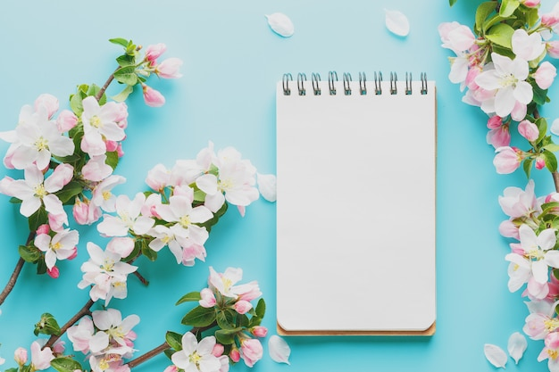 Blooming spring sakura on a blue background with notepad space for a message. low contrast