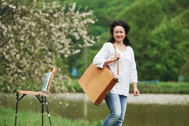 뒤에 피는 나무. 악기 케이스를 든 성숙한 화가가 아름다운 봄 공원에서 산책
