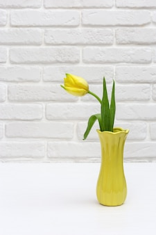 Blooming tulip flowers in small yellow vase on white brick wall in room. bouquet of flowers as spring gift  for womans or mothers day. vertical format.