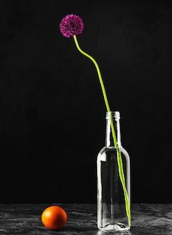 ガラスの水筒と生卵に咲く野生のタマネギ