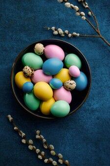 ボウルに咲く柳の枝とイースターエッグ。春の木の花とパスカル料理、休日のお祝いのための新鮮な花の装飾、イベントのシンボル
