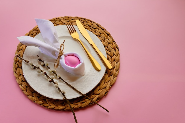 Blooming willow branch, easter egg on plate and tableware on pink background