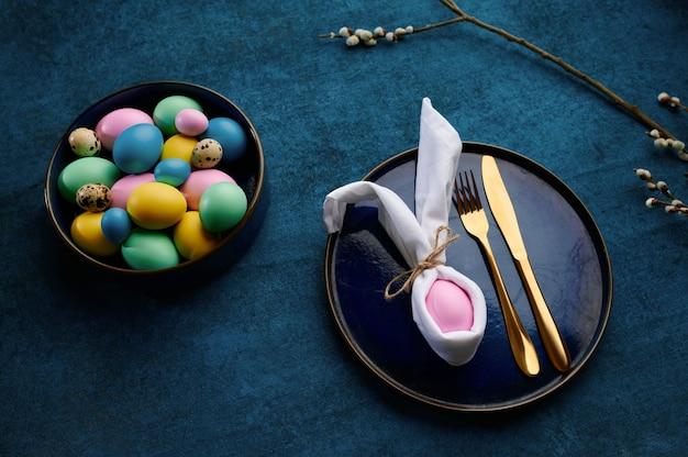 咲く柳の枝、ボウルにイースターエッグ、青い布の背景に食器