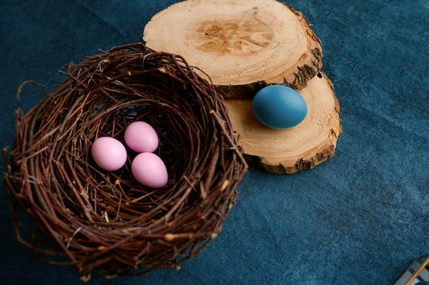 咲く柳の枝、巣のイースターエッグ、青い布の背景に食器