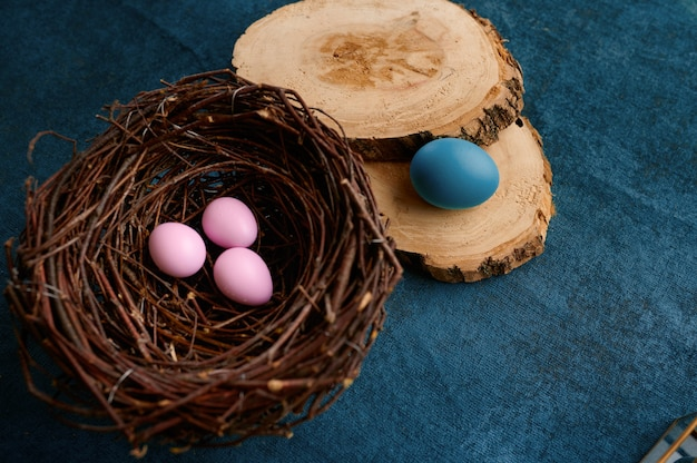 Blooming willow branch, easter eggs in nest and tableware on blue cloth background