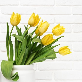 Blooming yellow flowers in white vase on decorative brick wall background with copy. spring flowers for womans or mothers day.