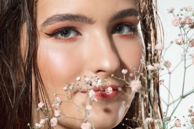 Цвести. закройте красивое женское лицо с нежными цветами на белом фоне. концепция косметики, макияжа, натуральных и экологических процедур, ухода за кожей. блестящая и здоровая кожа, мода, здравоохранение.