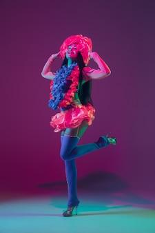 꽃. 네온 불빛에 보라색 벽에 하와이 갈색 머리 모델. 웃고, 춤추고, 재미 전통 옷을 입고 아름다운 여성. 밝은 휴일, 축하 색상, 축제.