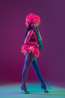 Fiorire. modello bruna hawaiano sulla parete viola alla luce al neon. belle donne in abiti tradizionali che sorridono, ballano e si divertono. vacanze luminose, colori di celebrazione, festival.