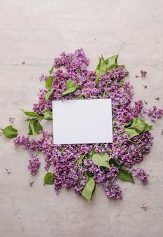 紫色の背景にライラックの花と花のモックアップフレーム