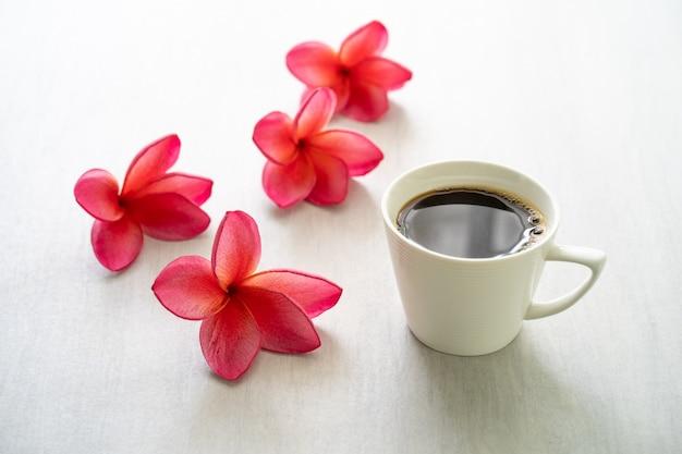 Plumeria цветения красный с кофе чашки на белой таблице.