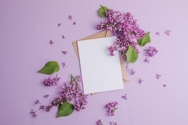 花のロマンチックな花の構成は、紫色の背景にライラックの花とフレームをモックアップします。