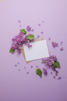 Blossom romantic flowers composition mock up frame with lilac flowers on purple background