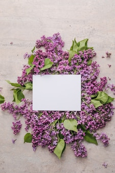 Blossom syringa vulgaris in lilac flower and blank paper card for text messagetop view romantic fl