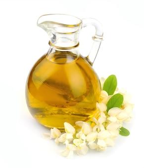 Цветущая акация с маслом на белом крупным планом