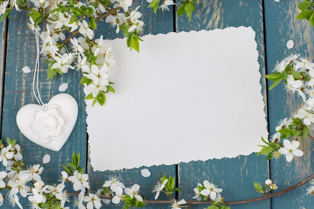 A blossoming apple tree branch, a heart and an empty sheet of paper