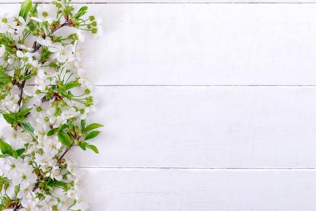 Цветущие ветви с молодыми листьями на белом деревянном фоне с копией пространства. весенний фон