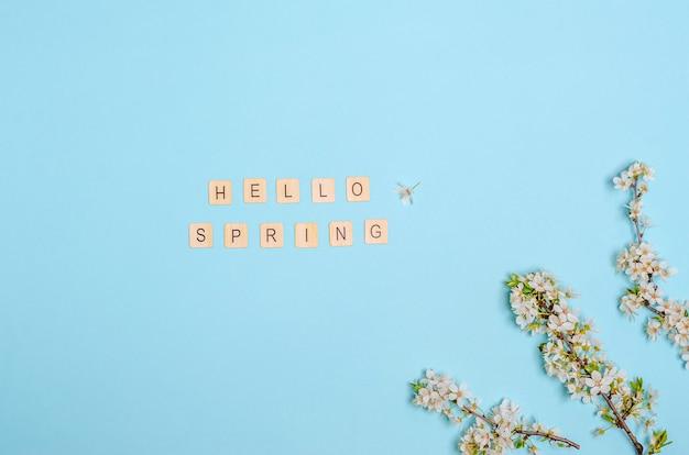 白い花と花の咲く桜の枝、青い背景にこんにちは春のテキスト。季節性のコンセプト、春。フラットレイ、コピースペース。上からの眺め。